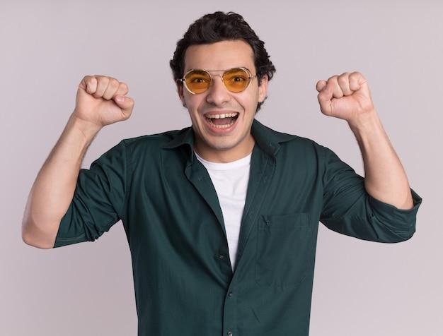 안경을 쓰고 녹색 셔츠에 젊은 남자가 흰 벽 위에 서있는 그의 성공을 기뻐하는 행복하고 흥분된 주먹 떨림