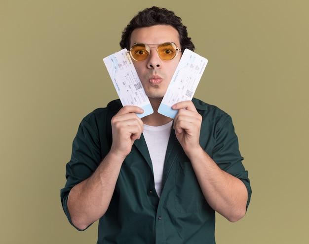 녹색 벽 위에 서 혼란 스 러 워 앞을보고 항공 티켓을 들고 안경을 쓰고 녹색 셔츠에 젊은 남자