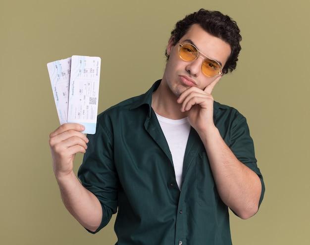 녹색 벽 위에 서 의아해 생각 서 정면을보고 항공 티켓을 들고 안경을 쓰고 녹색 셔츠에 젊은 남자