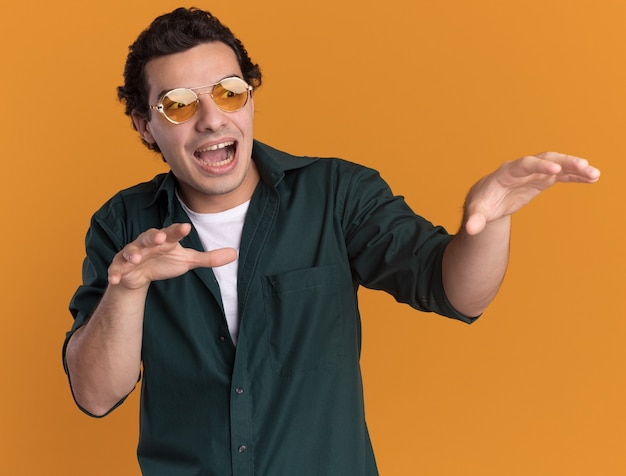 オレンジ色の壁の上に立って手をつないで興奮して驚いて脇を見て眼鏡をかけている緑のシャツを着た若い男