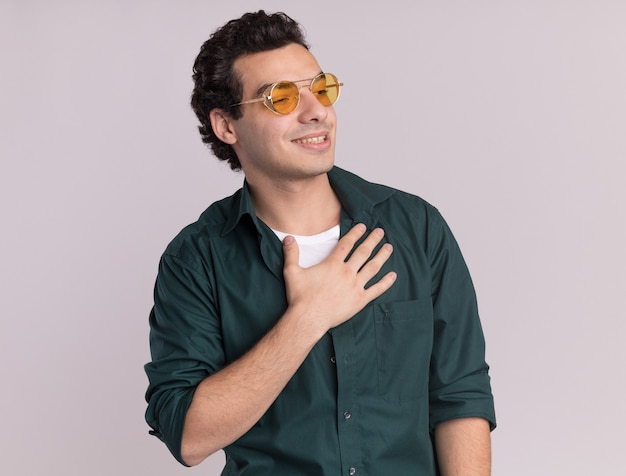 Молодой человек в зеленой рубашке в очках смотрит в сторону, держа руку на груди, улыбаясь, чувствуя благодарность, стоя над белой стеной