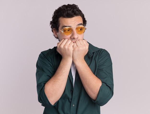 白い壁の上に立っているストレスと神経質な噛む爪を脇に見ている眼鏡をかけている緑のシャツを着た若い男