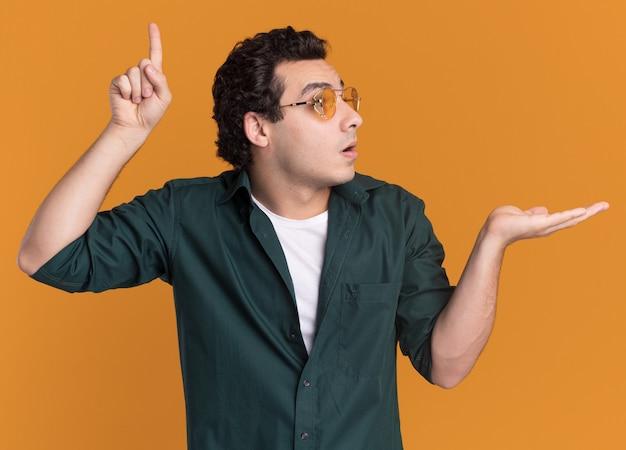 オレンジ色の壁の上に立っている腕のコピースペースを提示して人差し指を上に向けて驚いて脇を見て眼鏡をかけている緑のシャツを着た若い男