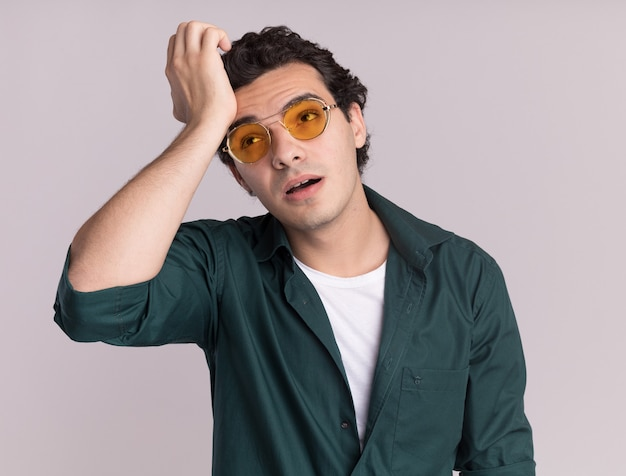 白い壁の上に立って疲れて退屈を脇に見ている眼鏡をかけている緑のシャツを着た若い男