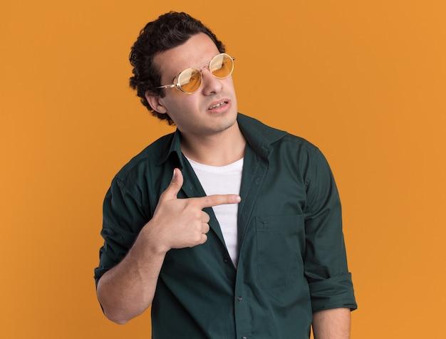 오렌지 벽 위에 서있는 측면을 검지 손가락으로 가리키는 심각한 얼굴로 옆으로 찾고 안경을 쓰고 녹색 셔츠에 젊은 남자