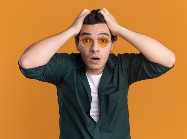 안경을 쓰고 녹색 셔츠를 입은 젊은 남자가 놀랐고 오렌지 벽 위에 서있는 그의 머리를 당기는 놀라움