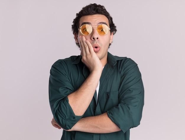 白い壁の上に立って驚いて驚いた正面を見て眼鏡をかけている緑のシャツを着た若い男