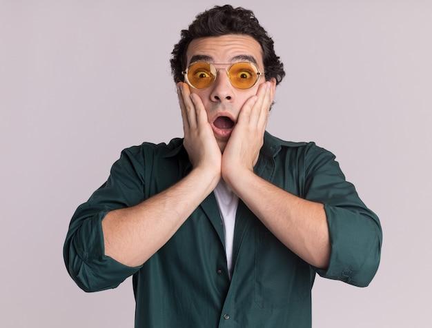 正面を見て眼鏡をかけている緑のシャツを着た若い男は、白い壁の上に立って驚いて驚いた