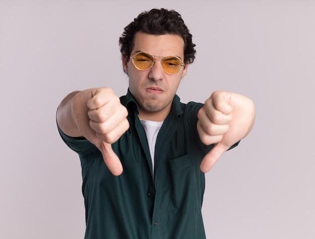 흰색 벽 위에 서 아래로 엄지 손가락을 보여주는 불쾌하고 전면을보고 안경을 쓰고 녹색 셔츠에 젊은 남자