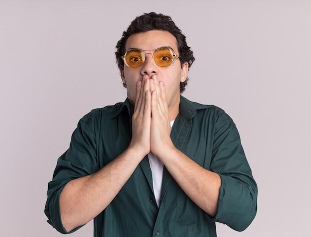 白い壁の上に立っている手で口を覆ってショックを受けている正面を見て眼鏡をかけている緑のシャツを着た若い男