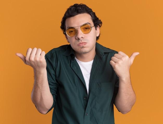 오렌지 벽 위에 서있는 측면에 엄지 손가락으로 가리키는 뺨을 불고 혼란스러운 전면을보고 안경을 쓰고 녹색 셔츠에 젊은 남자
