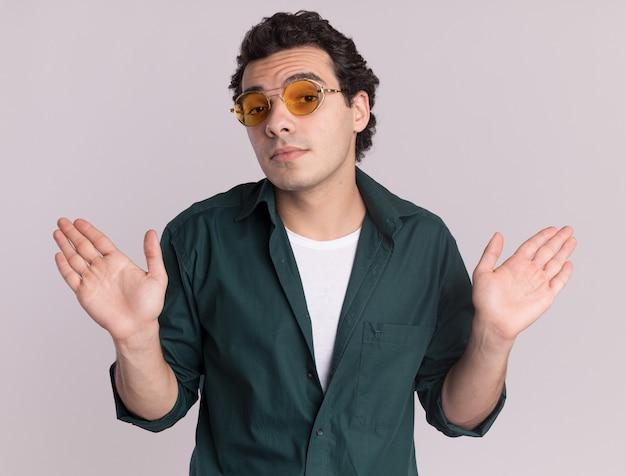 Молодой человек в зеленой рубашке в очках смотрит вперед, смущенный поднятыми руками, не имея ответа, стоит над белой стеной