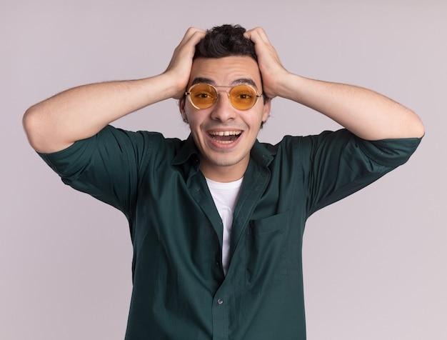 白い壁の上に立っている彼の頭の上の手で幸せで興奮している正面を見て眼鏡をかけている緑のシャツの若い男
