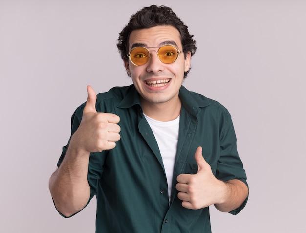 白い壁の上に立って親指を元気に見せて幸せで前向きな笑顔の正面を見て眼鏡をかけている緑のシャツを着た若い男
