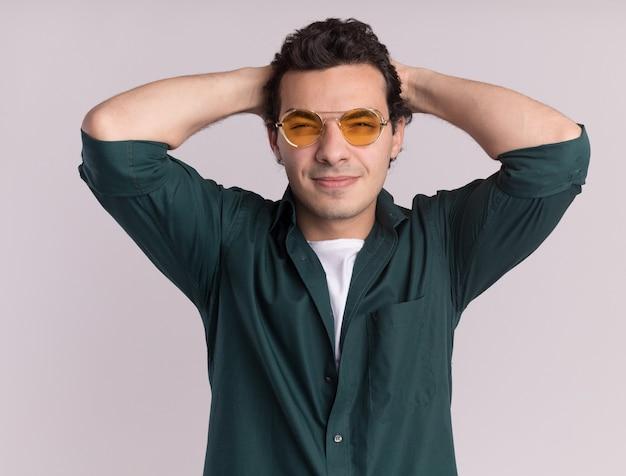 白い壁の上に立っている彼の頭の後ろの手で幸せで前向きな正面を見て眼鏡をかけている緑のシャツの若い男