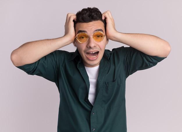 白い壁の上に立っている彼の頭の上の手で幸せと驚きの正面を見て眼鏡をかけている緑のシャツを着た若い男