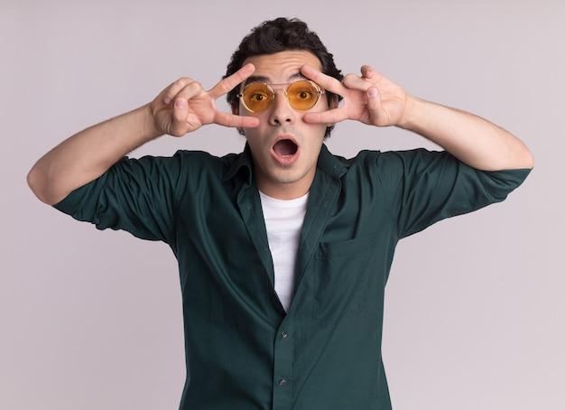 Молодой человек в зеленой рубашке в очках смотрит вперед, показывая знак v рядом с глазами, удивлен, стоя над белой стеной
