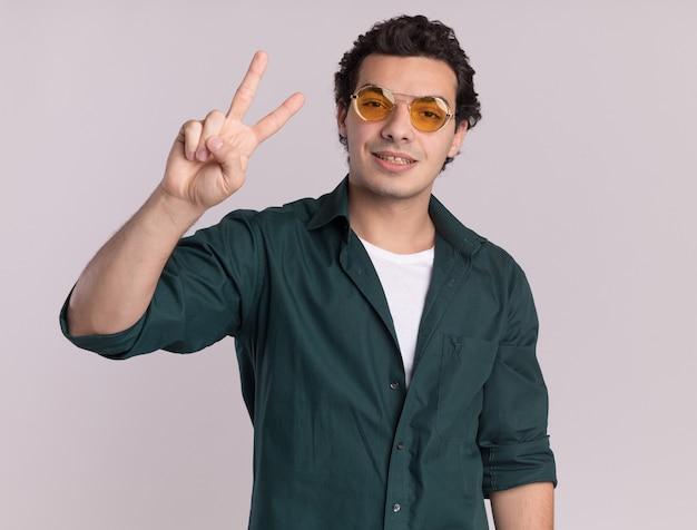 白い壁の上に立っている2番目を示す自信を持って正面を見て眼鏡をかけている緑のシャツの若い男