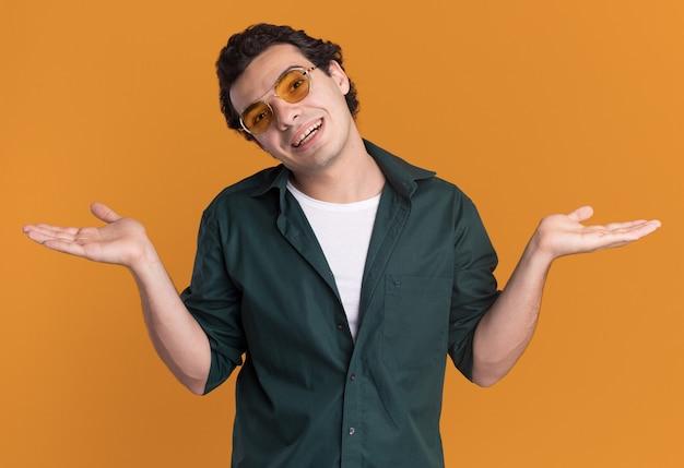 오렌지 벽 위에 서있는 측면에 팔을 펼치고 웃는 전면을보고 안경을 쓰고 녹색 셔츠에 젊은 남자