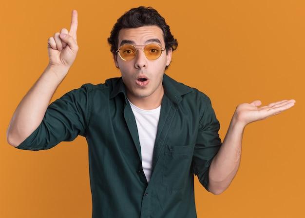 オレンジ色の壁の上に立っている腕のコピースペースを提示して人差し指を上に向けて驚いた正面を見て眼鏡をかけている緑のシャツの若い男