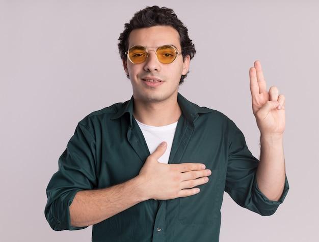 가슴과 손가락에 손으로 맹세하는 앞에서 안경을 쓰고있는 녹색 셔츠에있는 젊은 남자, 흰 벽 위에 서있는 미소 충성도 약속 만들기