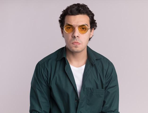 白い壁の上に立っている怒りの口を作る怒った顔で正面を見て眼鏡をかけている緑のシャツの若い男