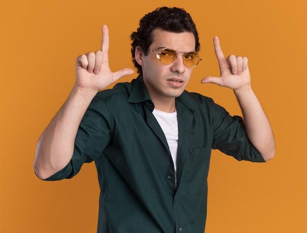 오렌지 벽 위에 서있는 손가락으로 권총 제스처를 만드는 자신감 식으로 정면을보고 안경을 쓰고 녹색 셔츠에 젊은 남자