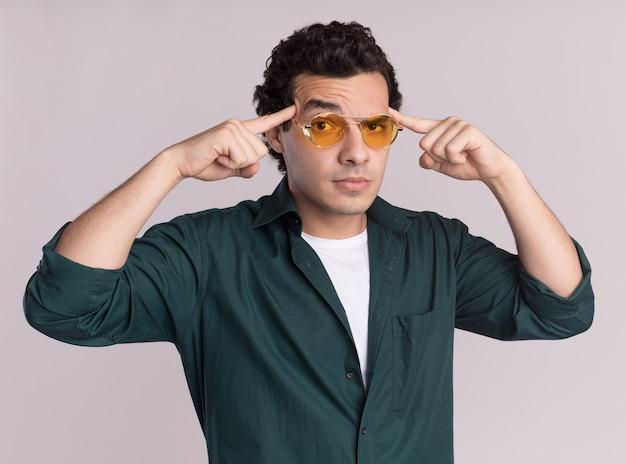 흰 벽 위에 서있는 그의 사원에서 검지 손가락으로 가리키는 똑똑한 얼굴에 자신감이 표정으로 앞을보고 안경을 쓰고 녹색 셔츠에 젊은 남자