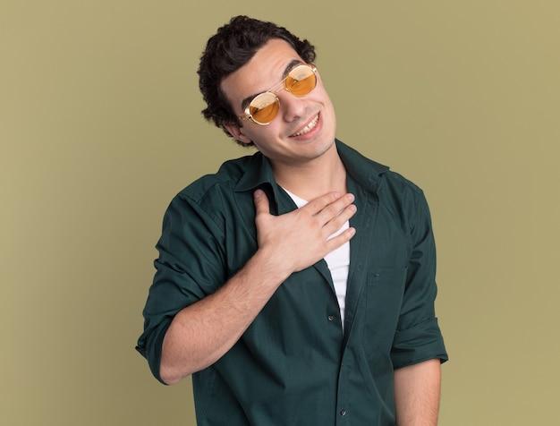 녹색 벽 위에 서있는 고마운 느낌의 그의 가슴에 손으로 정면을보고 안경을 쓰고 녹색 셔츠에 젊은 남자