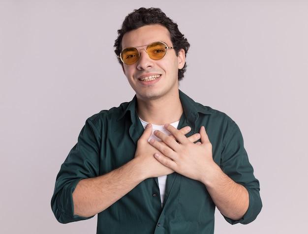 Молодой человек в зеленой рубашке в очках смотрит вперед, положив руки на грудь, чувствуя благодарность, стоя над белой стеной