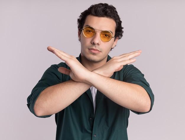 Молодой человек в зеленой рубашке в очках смотрит вперед с серьезным лицом, скрестив руки, останавливает жест, стоя над белой стеной