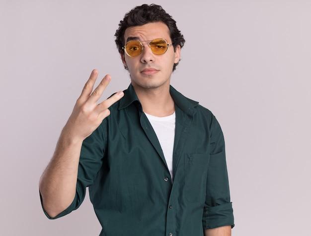 Молодой человек в зеленой рубашке в очках смотрит вперед с серьезным лицом, показывая номер три, стоящий над белой стеной