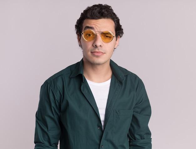 흰색 벽 위에 서 회의적인 미소로 정면을보고 안경을 쓰고 녹색 셔츠에 젊은 남자