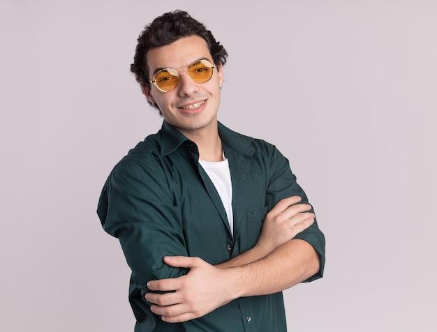 팔을 얼굴에 미소로 정면을보고 안경을 쓰고 녹색 셔츠에 젊은 남자가 흰 벽 위에 서 넘어