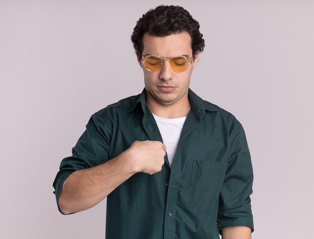 흰 벽 위에 서있는 자신을 가리키는 혼란스러워 보이는 안경을 쓰고 녹색 셔츠에 젊은 남자