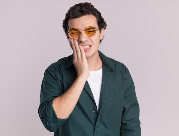 흰 벽 위에 서있는 그의 입에 손으로 혼란스러워 보이는 안경을 쓰고 녹색 셔츠에있는 젊은 남자
