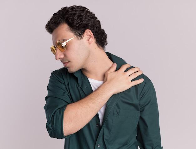 眼鏡をかけている緑のシャツを着た若い男は、白い壁の上に立っている痛みを感じて肩に触れて体調を崩しているように見えます