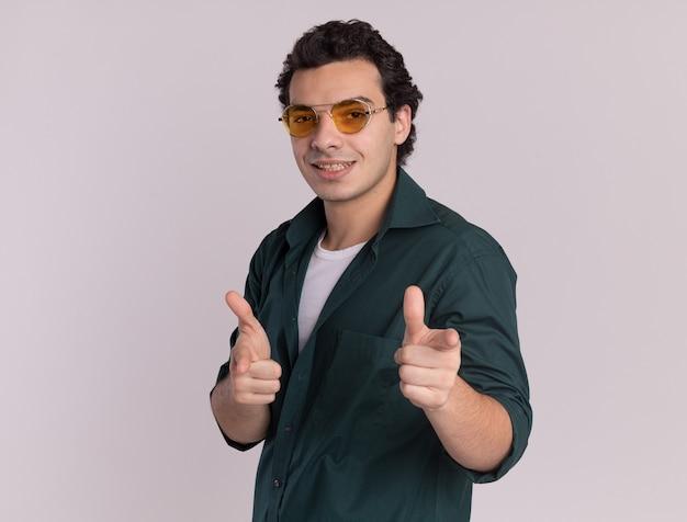 흰 벽 위에 행복하고 긍정적 인 서 앞에 검지 손가락으로 가리키는 안경을 쓰고 녹색 셔츠에 젊은 남자