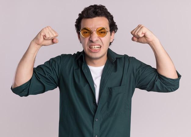 화가 난 얼굴로 정면을보고 주먹을 올리는 안경을 쓰고 녹색 셔츠에있는 젊은 남자는 흰 벽에 야생 서가는 좌절