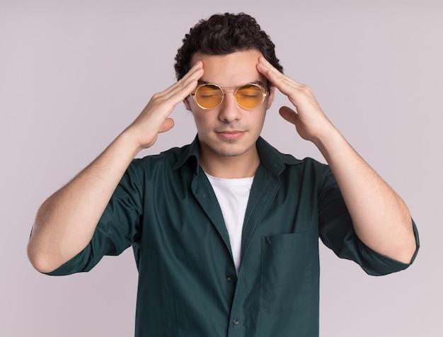 Молодой человек в зеленой рубашке в очках трогает голову усталым и перегруженным работой с головной болью, стоящей над белой стеной