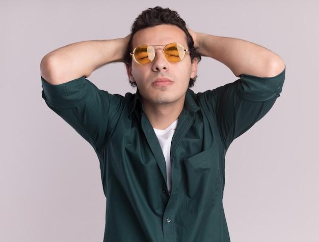 白い壁の上に立っている彼の頭の後ろの手に悩まされている目を閉じて眼鏡をかけている緑のシャツを着た若い男