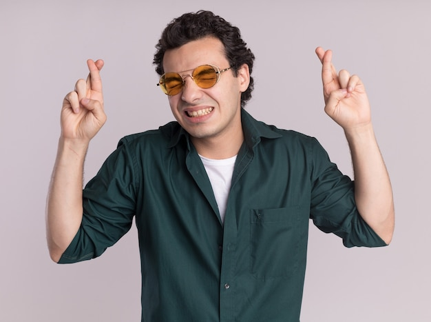 흰 벽 위에 서있는 바람직한 소원을 만드는 희망 표현으로 손가락을 건너는 닫힌 눈으로 안경을 쓰고 녹색 셔츠에 젊은 남자