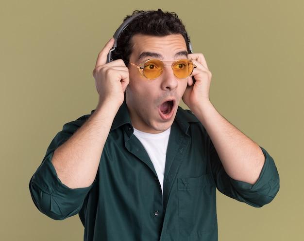 헤드폰으로 안경을 쓰고 녹색 셔츠를 입은 젊은 남자가 녹색 벽 위에 서서 놀라게하고 놀란다.