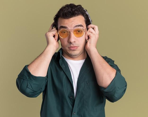 녹색 벽 위에 서 혼란 스 러 워 앞을보고 헤드폰으로 안경을 쓰고 녹색 셔츠에 젊은 남자