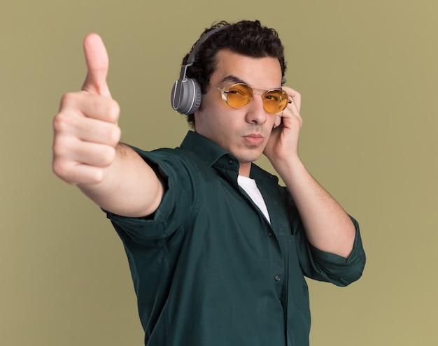 녹색 벽 위에 서 엄지 손가락을 보여주는 심각한 얼굴로 정면을 바라 보는 헤드폰으로 안경을 쓰고 녹색 셔츠에 젊은 남자