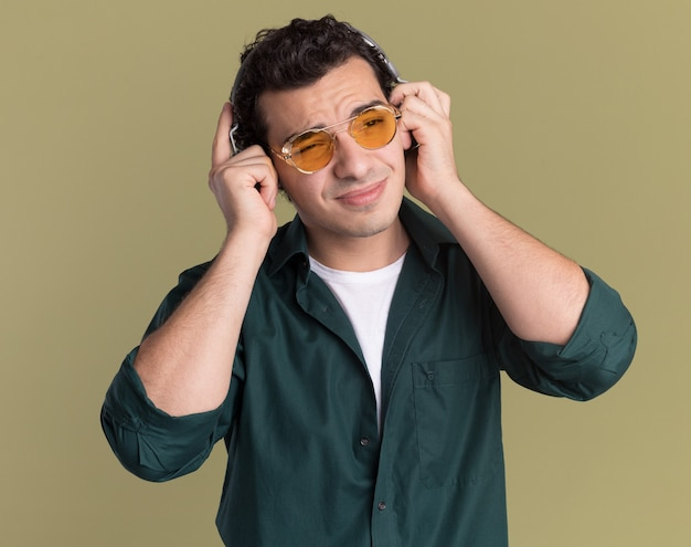 녹색 벽 위에 서있는 혼란스럽고 불쾌한 좋아하는 음악을 찾고 헤드폰으로 안경을 쓰고 녹색 셔츠에 젊은 남자