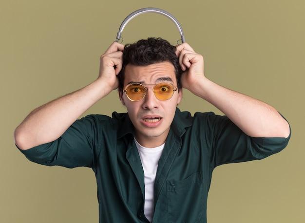 彼の頭の上にヘッドフォンで眼鏡をかけている緑のシャツを着た若い男は混乱し、緑の壁の上に立って驚いた