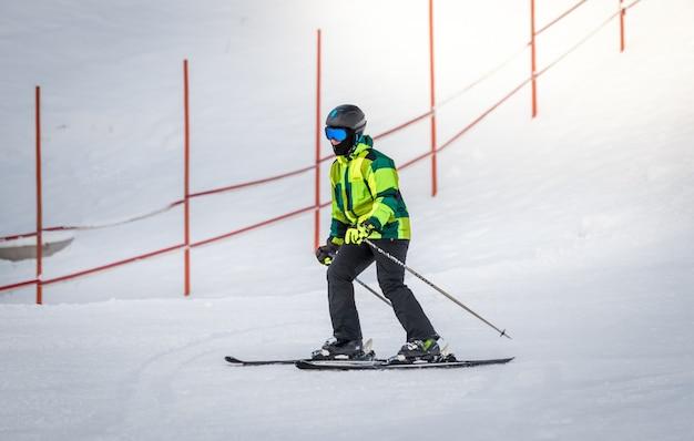 Молодой человек в зеленом костюме катается на лыжах с холма