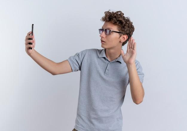 회색 폴로 셔츠에 젊은 남자가 흰 벽 위에 서있는 미소를 손으로 흔들며 셀카를하고 스마트 폰을 들고