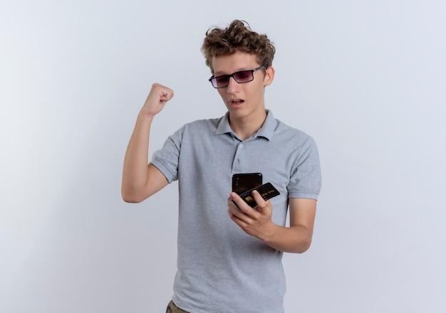 白い壁の上に立って幸せで興奮して拳を握りしめているクレジットカードを保持している彼のスマートフォンの画面を見ている灰色のポロシャツの若い男